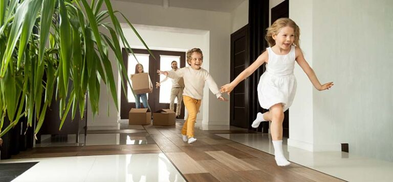 Happy Young Family and Excited Children Entering Brand-New Home