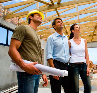 Young Couple Look At Home Plans with Builder