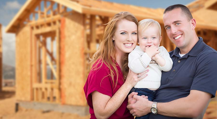 Happy Young Family Outside Their New Home Framing at the Construction Site