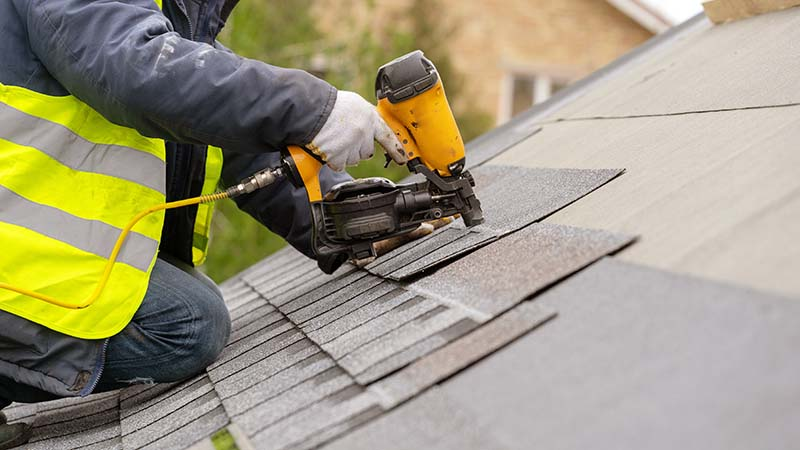 Roofer in Special Protective Work Wear Installing New Shingles in Home Roof